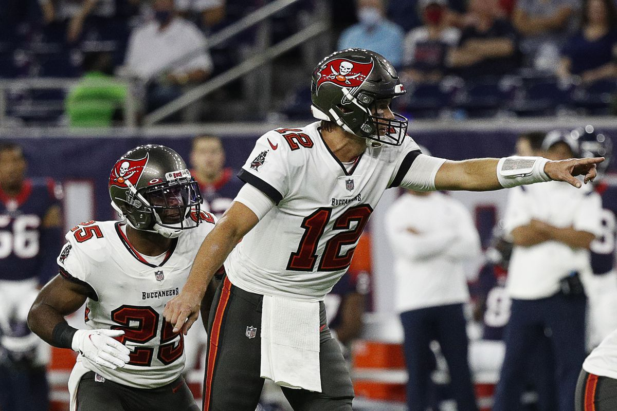 Tom Brady of the Tampa Bay Buccaneers points out the defense as Giovani Bernard goes in motion against the Houston Texans during a NFL preseason game at NRG Stadium on August 28, 2021 in Houston, Texas.