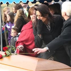 Family members place roses on the casket of former Utah Gov. Olene Walker during a graveside service at the Salt Lake City Cemetery in Salt Lake City on Friday, Dec. 4, 2015. Walker died of natural causes at age 85.