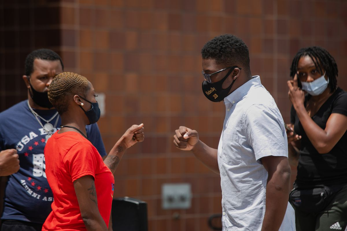 Community organizer Ja'Mal Green fist bumps his colleague after a press conference in front of the Chicago Police Department's headquarters on June 23, 2020. Green called on Mayor Lori Lightfoot to address the root causes of violence, cancel the $33 million contract between the Chicago Police Department and Chicago Public Schools and re-allocate $500 million from the police budget to better social services. | Pat Nabong/Sun-Times