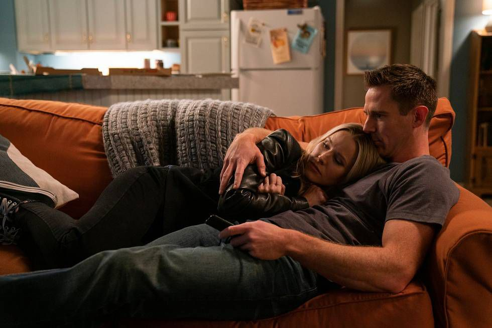 Kristen Bell as Veronica Mars and Jason Doing as Logan are losing on the couch.