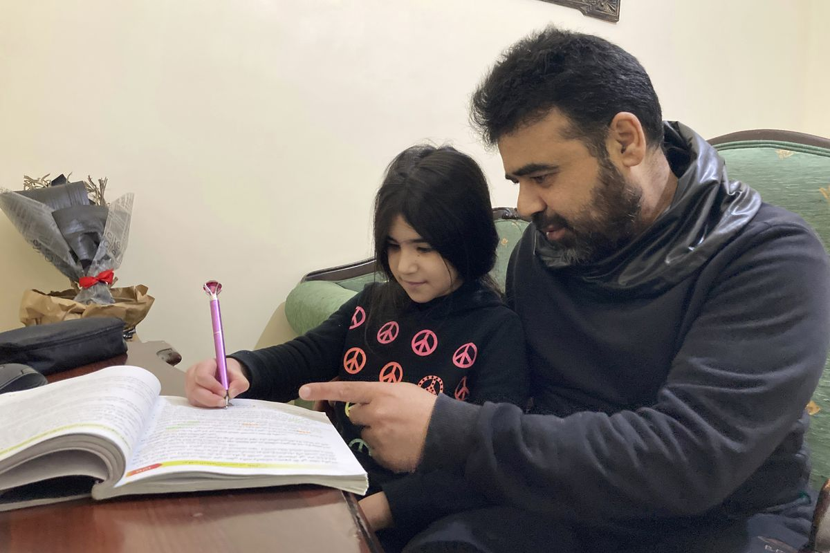 Syrian refugee Mahmoud Mansour, 47, helps his youngest daughter Sahar, 8, with her homework at his rented apartment in Amman, Jordan, Wednesday, Jan. 20, 2021.