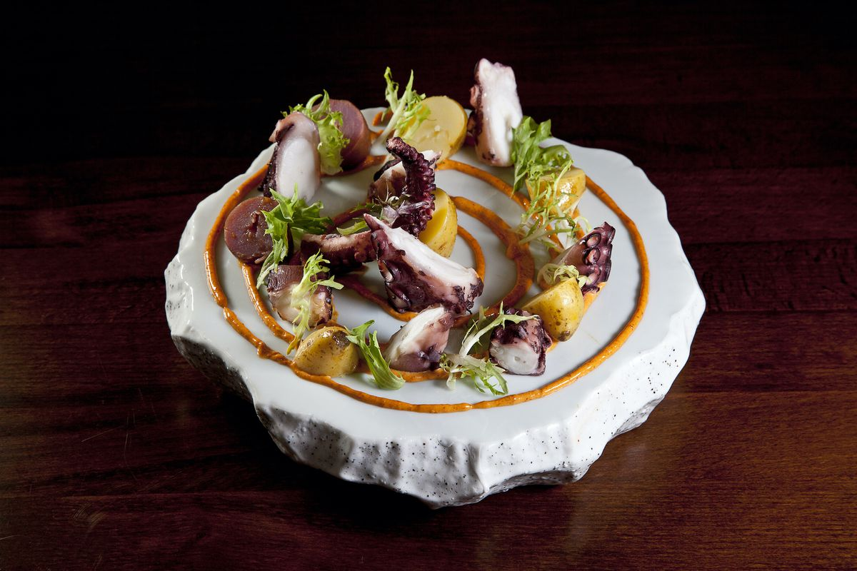 Severed octopus tentacles are arranged on a plate alongside greens and a swirl of orange sauce