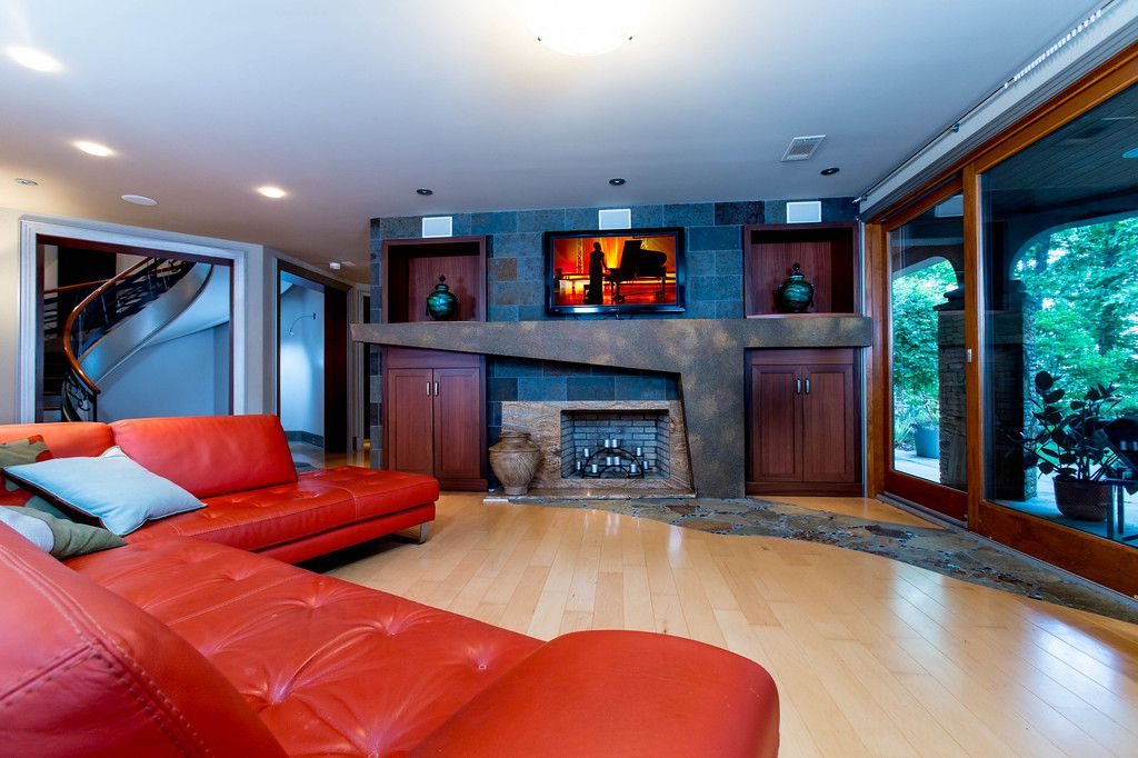 A big room with a fireplace and red couch.