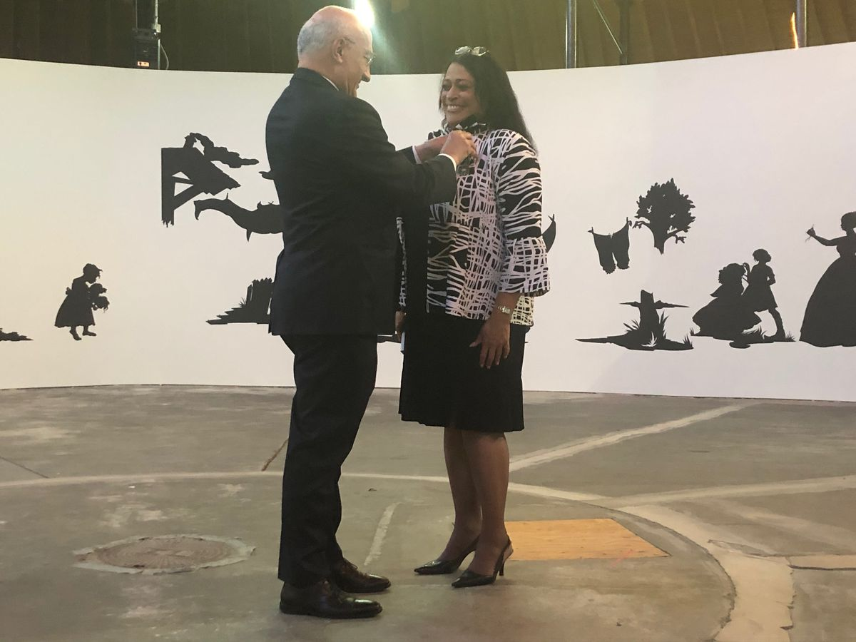 Philippe Etienne, Ambassador of France to the United States, pins The Order of Arts and Letters medal, the French government's highest honor in the arts, onto DuSable Museum of African American History President & CEO Perri Irmer in a ceremony Monday night.