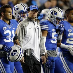 head coach Bronco Mendenhall of the Brigham Young University Cougars walks with his team during a time out in the fourth quarter against USU during NCAA football in Provo, Friday, Oct. 3, 2014.