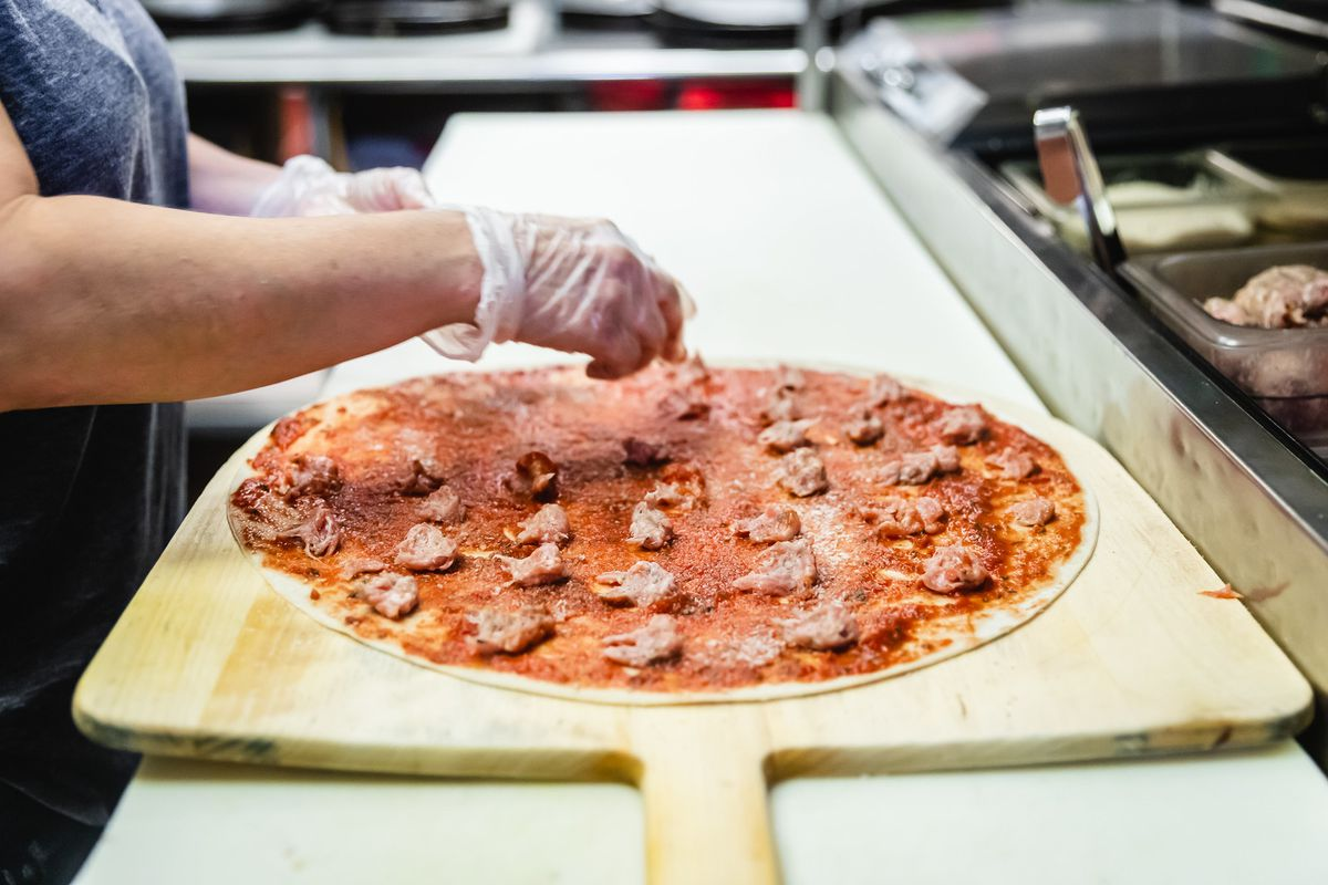 Topping pizza with ground pork sausage.