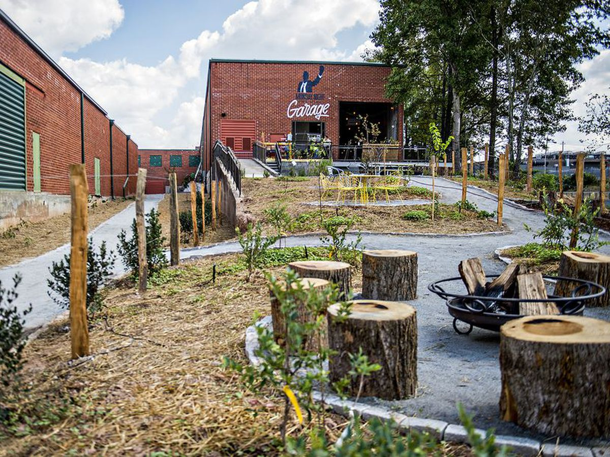 An outdoor fire pit area and warehouse that's been turned into a beer brewery.