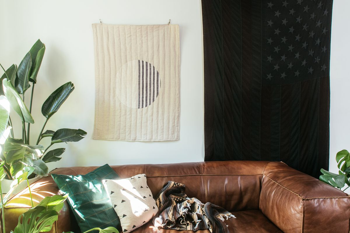 A brown leather couch sits against a painted white wall. There are assorted throw pillows on the couch. On the wall hang two tapestries with art. There is a large houseplant next to the couch.