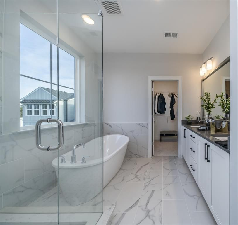 A white master bathroom with a standalone tub.