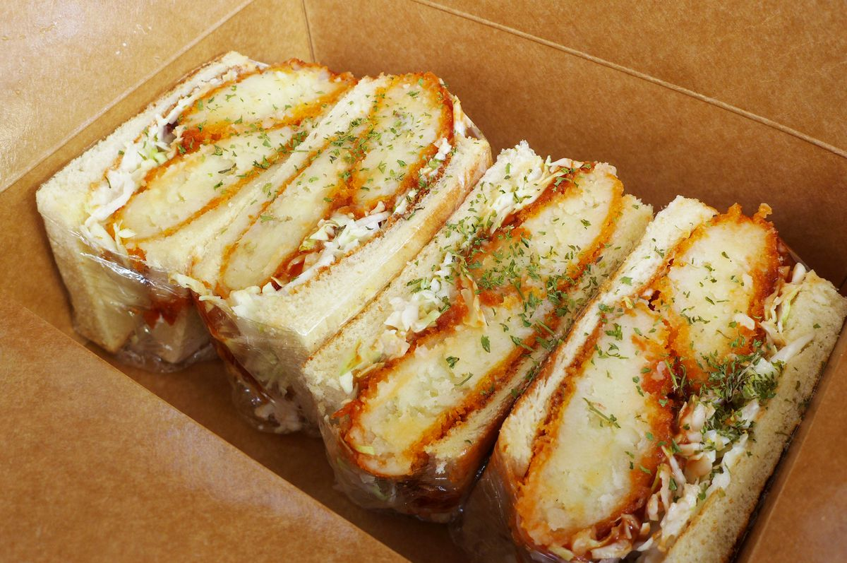 In a cardboard box a sandwich of fried potato croquettes in slices of white bread, cut into four perfectly symmetrical quarters.
