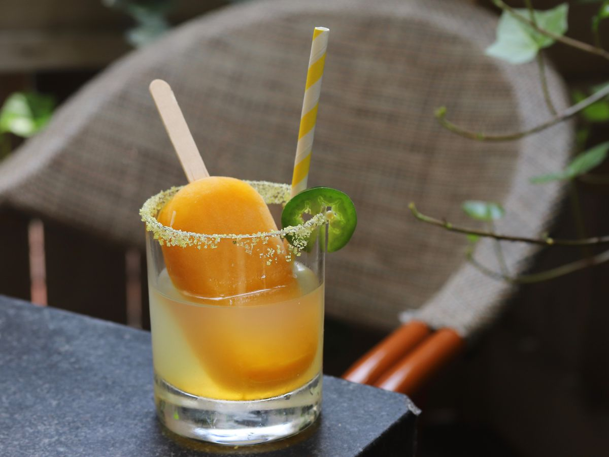 An orange popsicle is dunked in a glass of a spicy margarita, which is garnished with a jalapeno slice. The glass is on a restaurant's patio table outside.