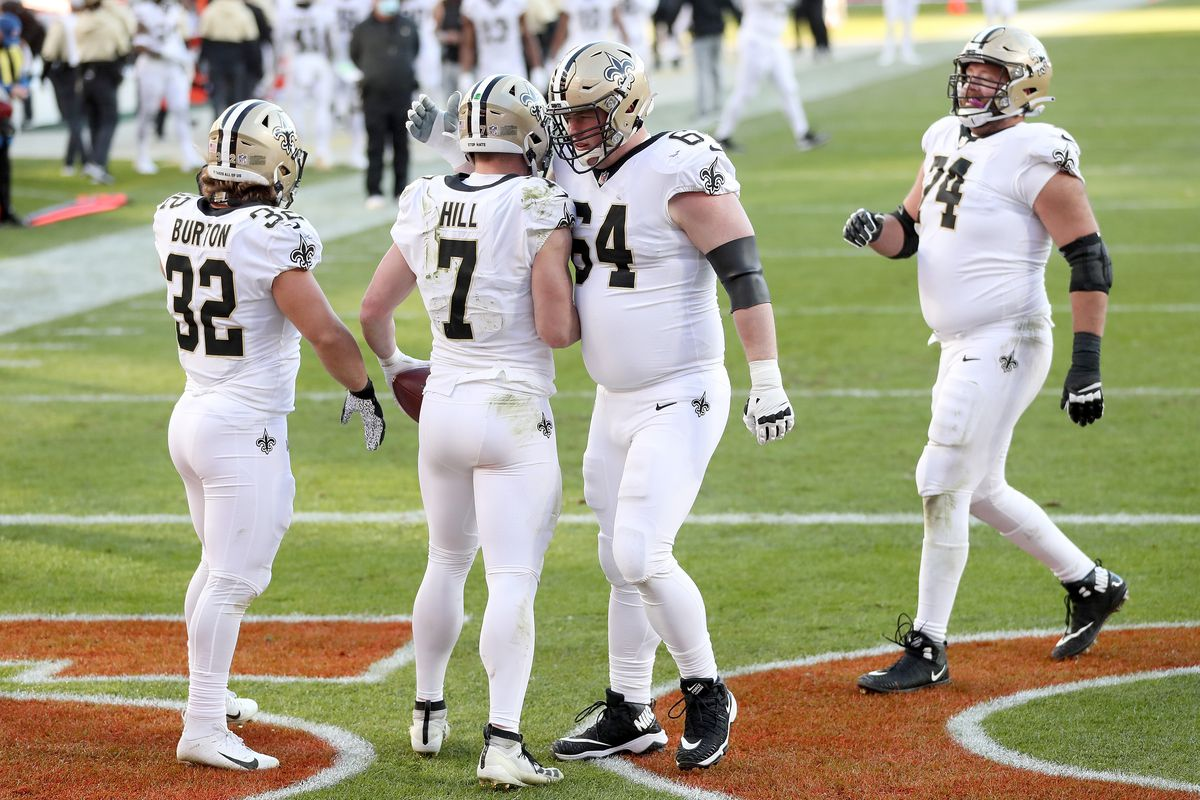 Taysom Hill #7 of the New Orleans Saints celebrates alongside Michael Burton #32, James Hurst #74, and Will Clapp #64 after rushing for a two yard touchdown during the second quarter of a game against the Denver Broncos at Empower Field At Mile High on November 29, 2020 in Denver, Colorado.