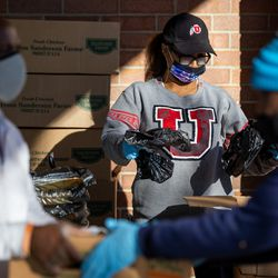 Nicole Tarleton, back, prepares packages of chicken while her husband, Vic Tarleton, left, and Al Noble, right, load a box of food into a waiting carat Calvary Baptist Church in Salt Lake City on Saturday, Dec. 19, 2020.