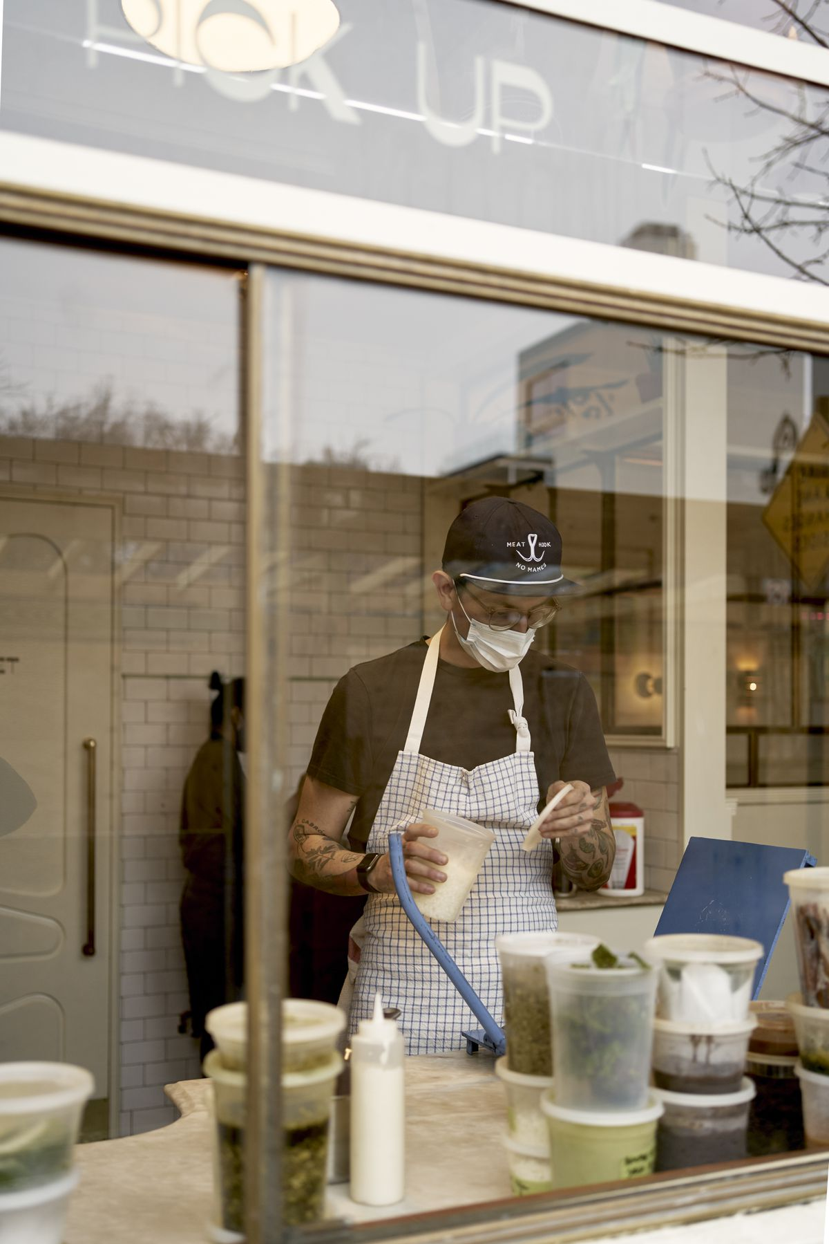 A person with a plaid apron on stands behind a pickup window measuring out ingredients. Sauces and ingredients are stacked in quart containers on the counter