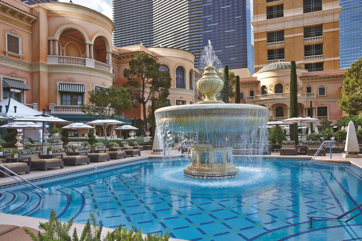 A pool with a fountain in the middle and cabanas on the side