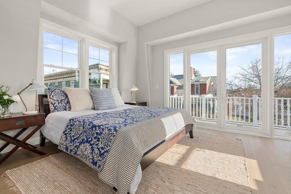 A bedroom with a bed, and the bedroom is in a sunny corner with plenty of windows.