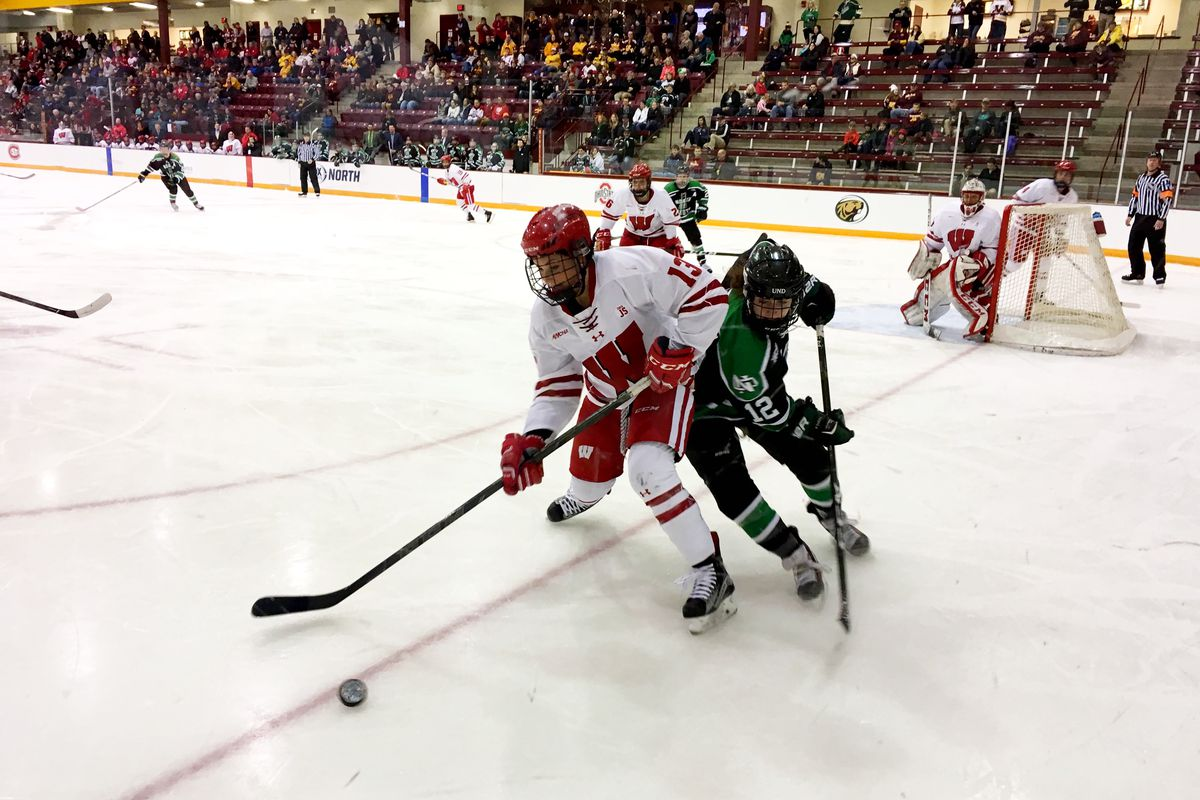 Ryleigh Houston (12) battling Maddie Rolfes (13) for the puck during the WCHA 2017 semifinals.