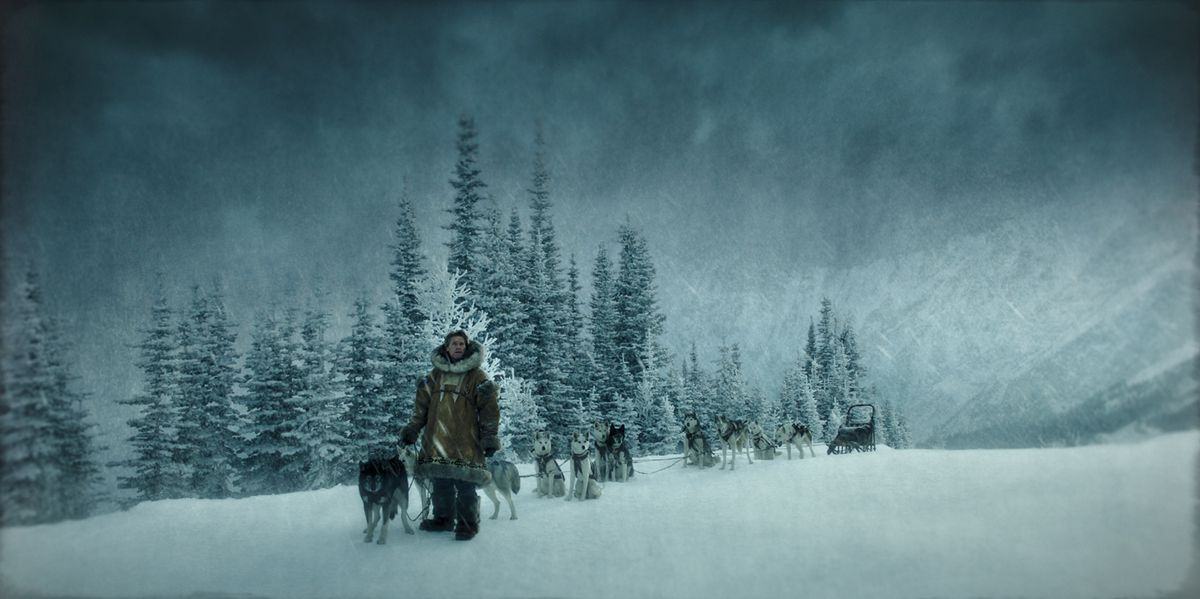 Seppala (Dafoe) stands, with his dogs, in the midst of snow-covered trees.