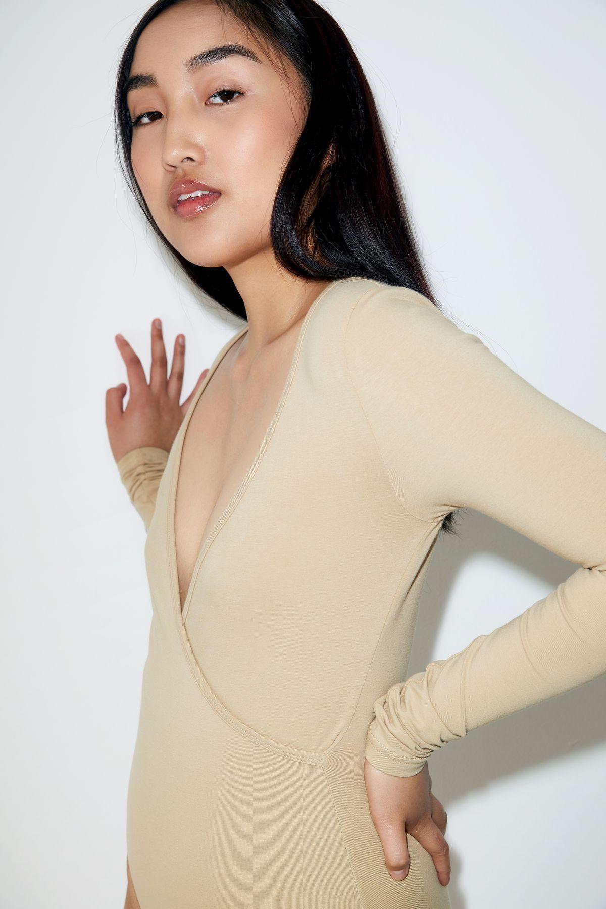 A model wears a nude bodysuit.