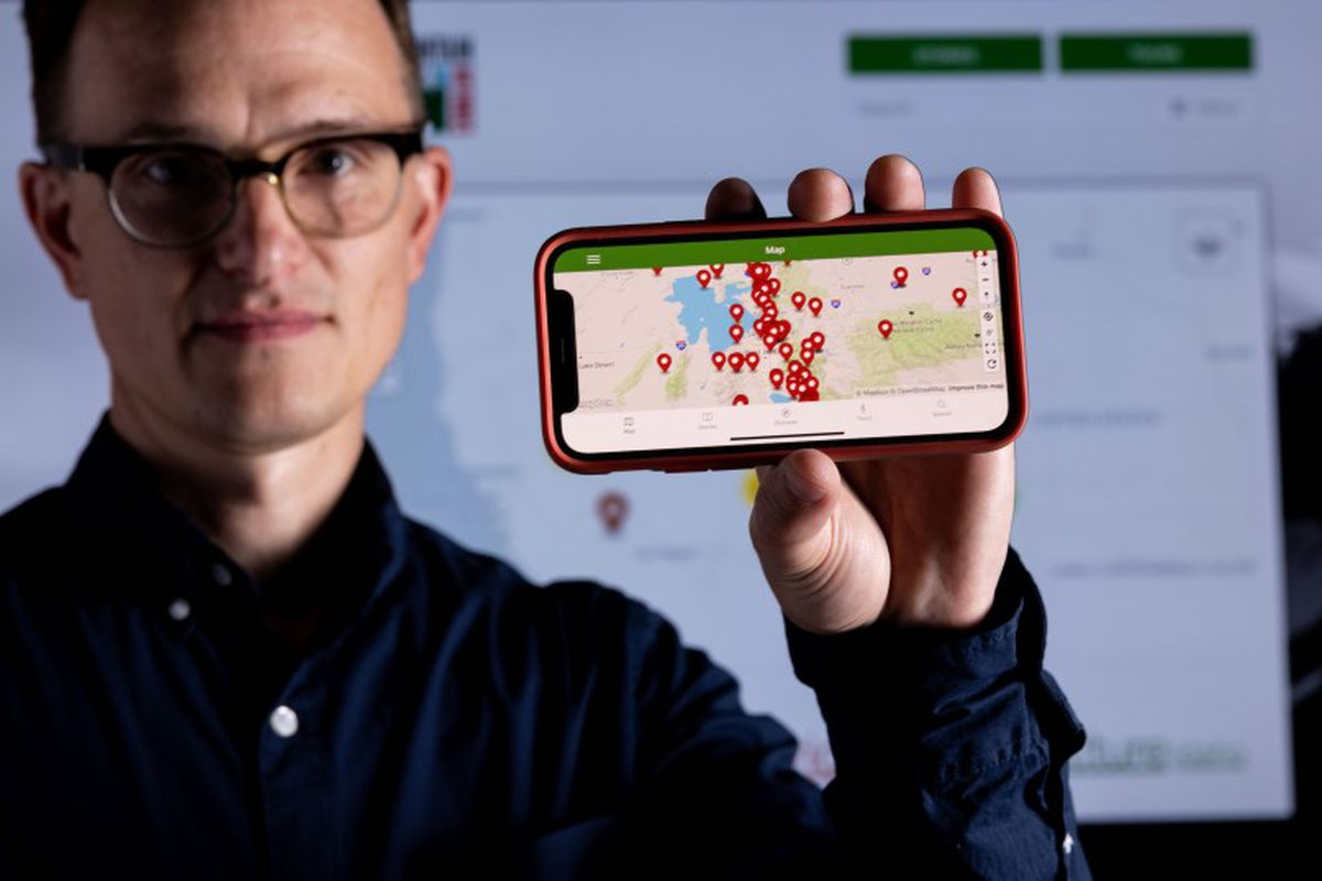 """BYU history professor Brenden Rensink holds up his phone displaying a new app called """"Intermountain Histories."""""""