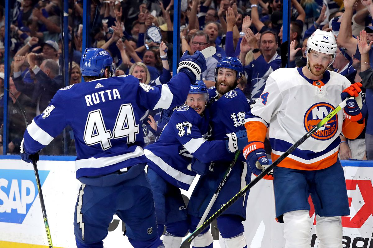Yanni Gourde #37 of the Tampa Bay Lightning is congratulated by Barclay Goodrow #19 and Jan Rutta #44 after scoring a goal as Scott Mayfield #24 of the New York Islanders reacts during the first period in Game Five of the Stanley Cup Semifinals during the 2021 Stanley Cup Playoffs at Amalie Arena on June 21, 2021 in Tampa, Florida.