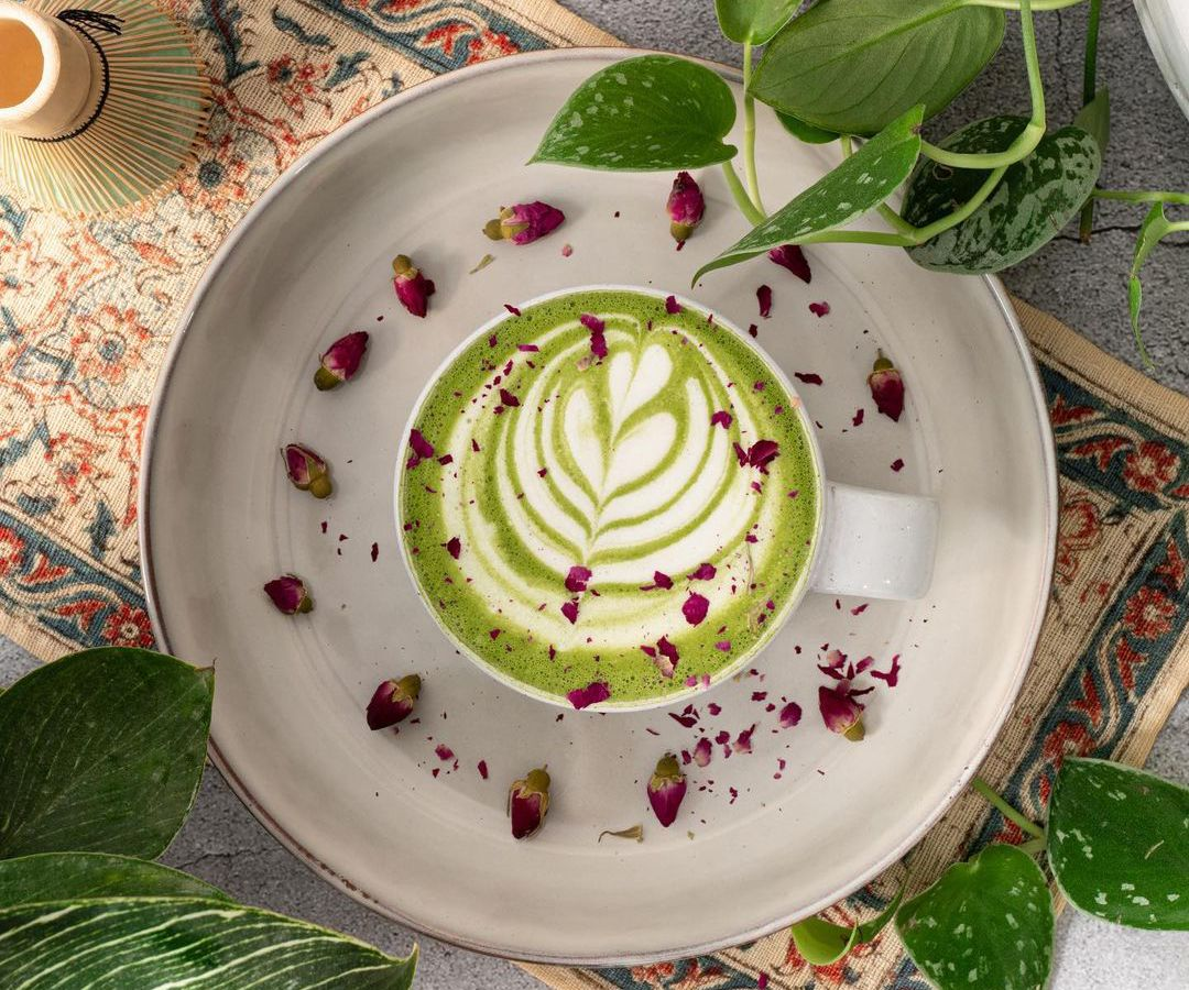 Overhead view of a matcha latte with decorative foam, strewn with rose petals. It sits on a vintage carpet-looking placemat, a match whisk to the side and green plants in the background.