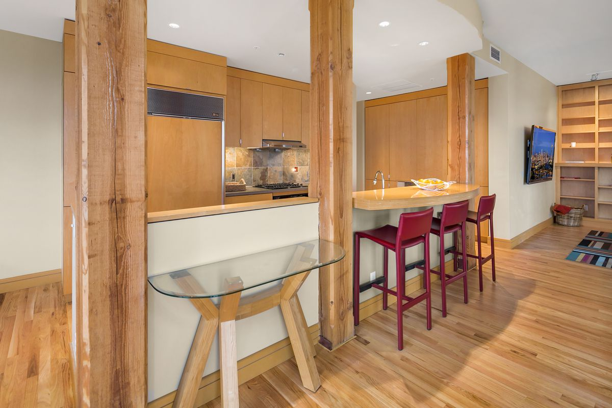 A kitchen with a breakfast bar and exposed wood columns.
