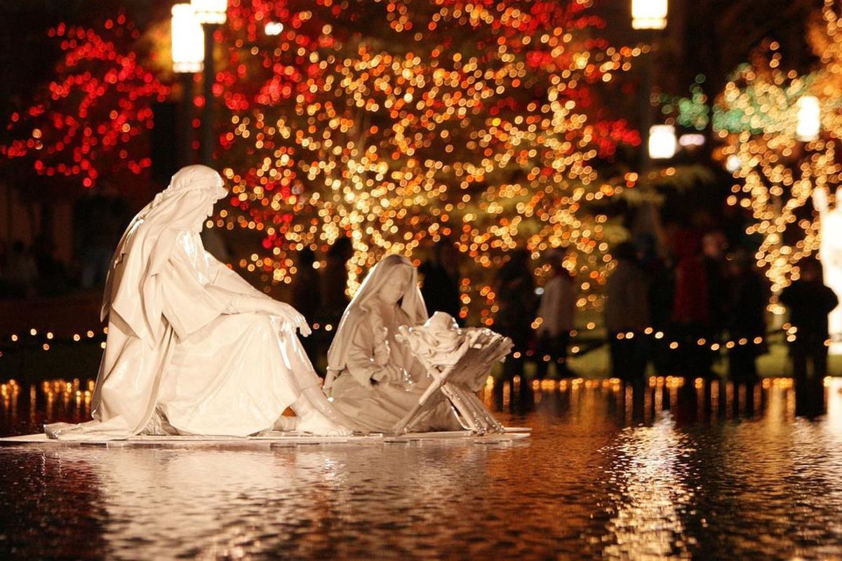 A nativity sits in the middle of reflecting pool as downtown visitors walk through the Church Plaza when Christmas lights were turned on downtown and at Temple Square in Salt Lake City on Friday, Nov. 25.