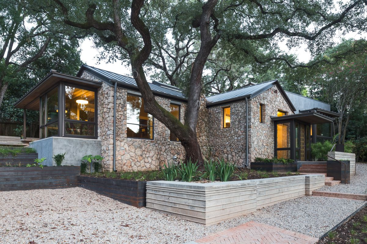 stone house with raised wooden and concrete garden beds