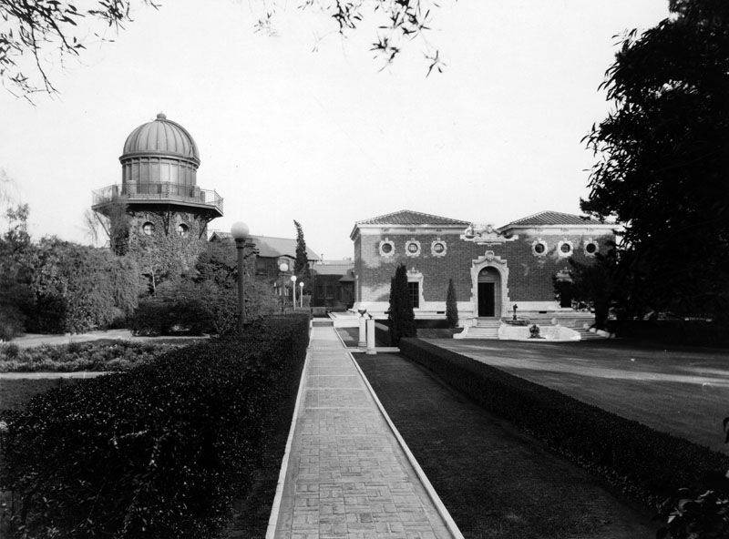 In the foreground is a sidewalk with grass on both sides. In the distance is a mansion with a domed tower.