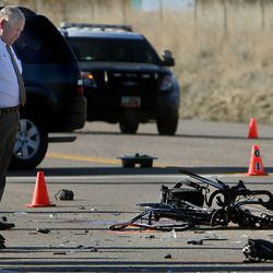 Lehi police officers investigate the scene where two bicyclists were hit by a pickup truck and died of their injuries in Lehi on Wednesday, March 12, 2014. Police said the cyclists were attempting to turn east near the intersection of Redwood Road and 2100 North just before 6 a.m. The driver of a pickup truck apparently did not see the pair and hit them.