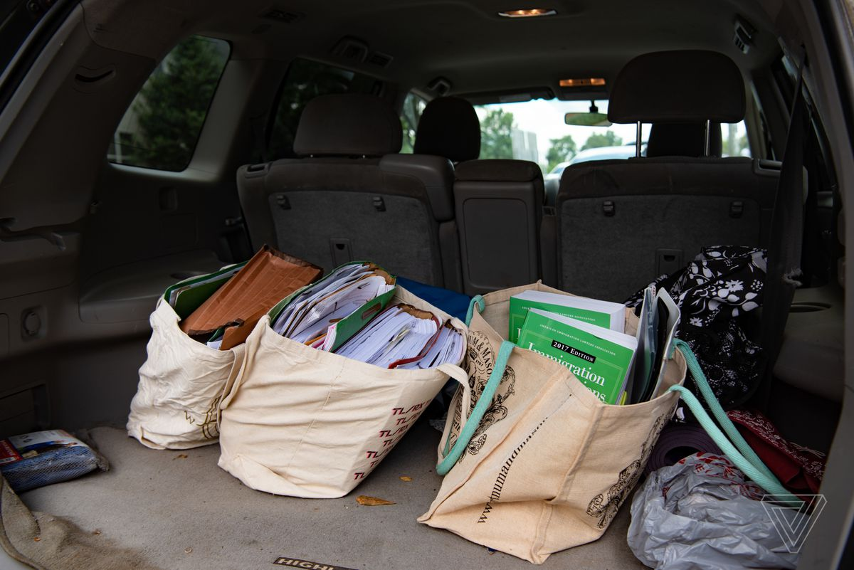 large bags of files and papers take up much of the trunk of a car.