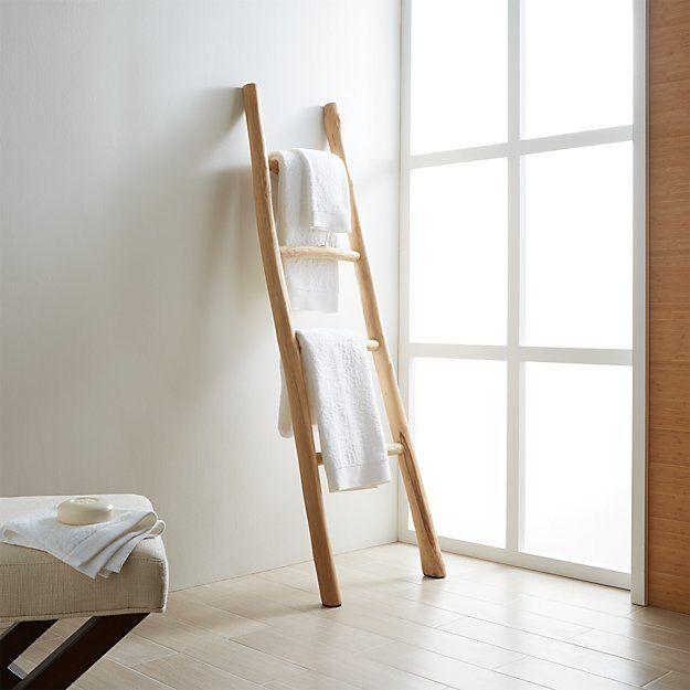 Light wood ladder leaning against white all.
