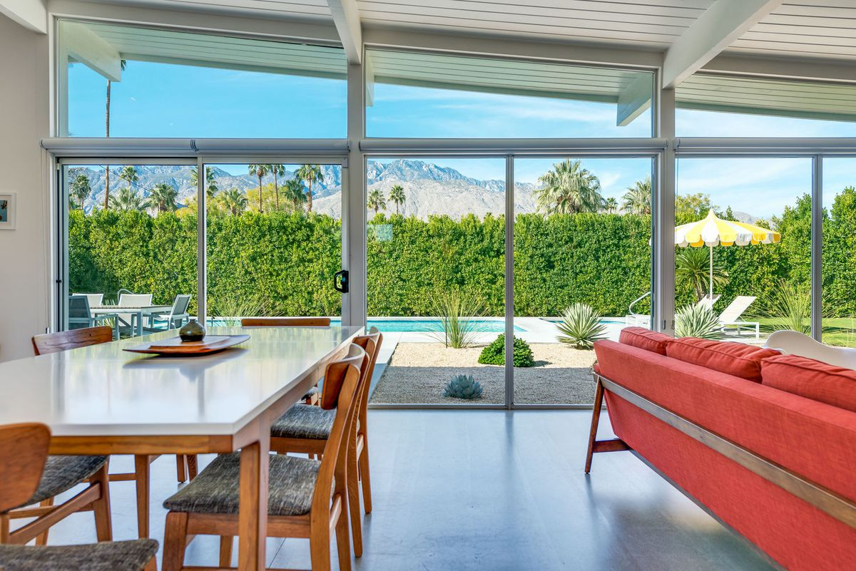 A dining room table and right red couch sit in front of floor-to-ceiling glass windows.