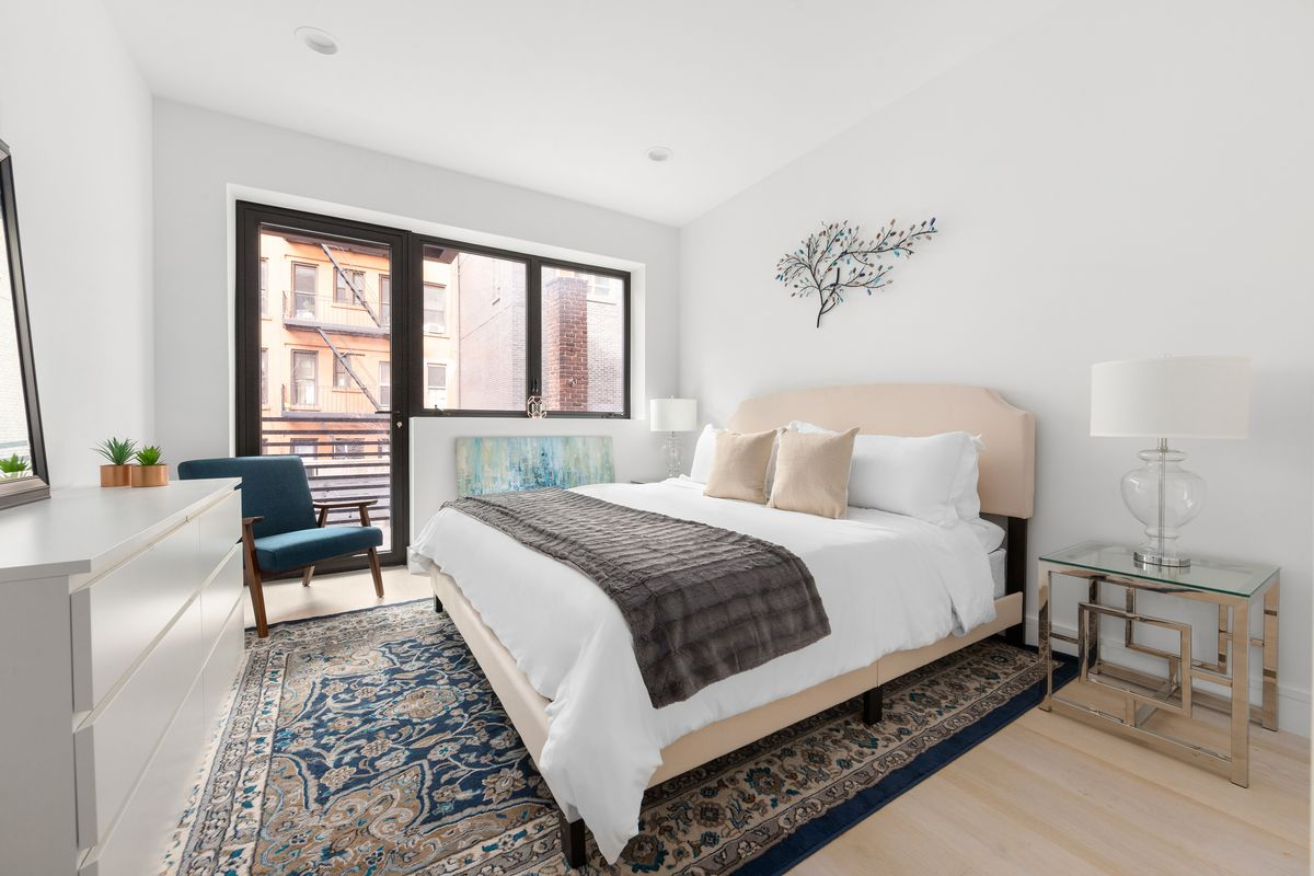A bedroom with a large bed, a large window, a door that leads to a balcony, and a colorful rug.