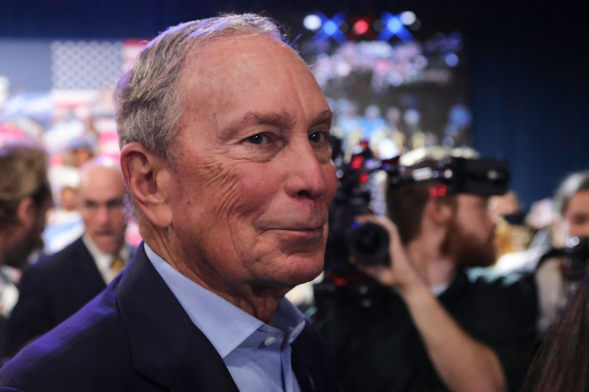Bloomberg in a navy suit and light blue shirt, his collar open, smiles as he stands amid a crowd of reporters.