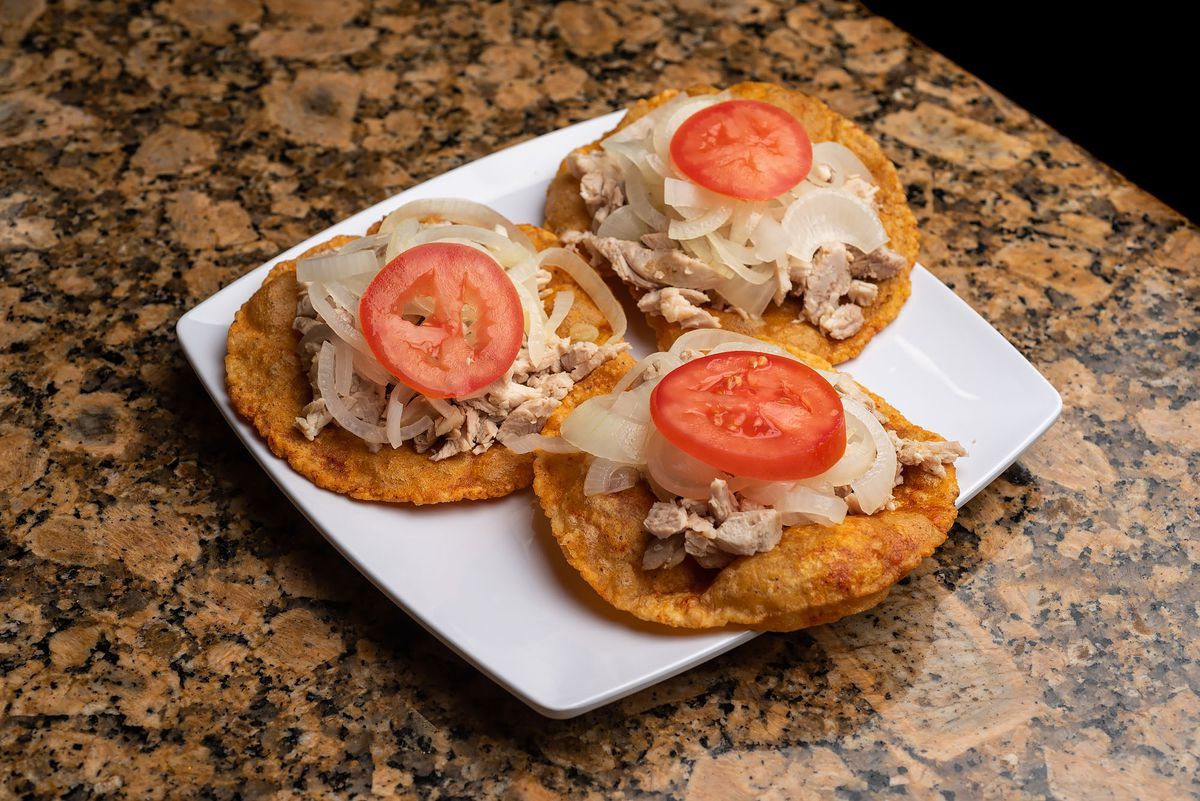 Salbutes, a puffed corn tortilla with shredded chicken and vegetables