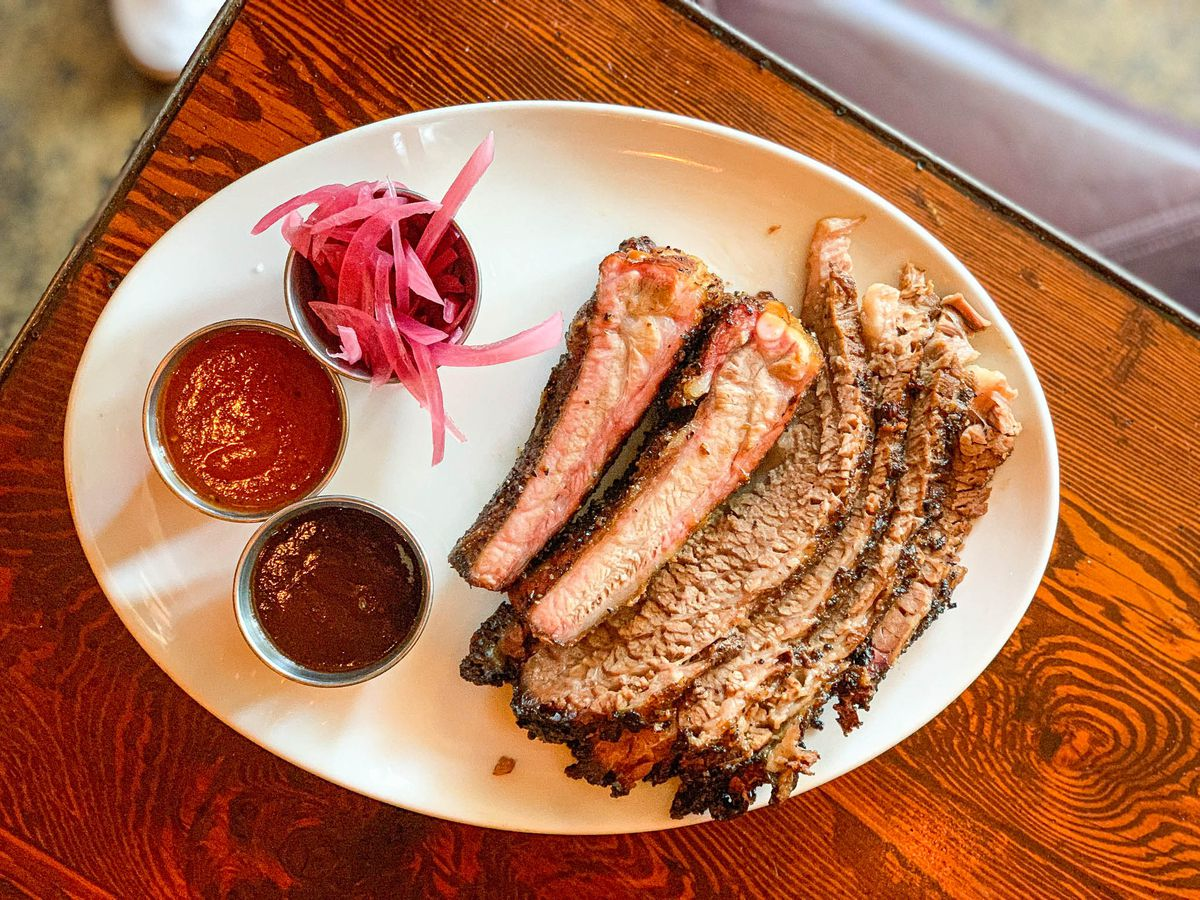A plate of brisket and ribs with sauce on the side.