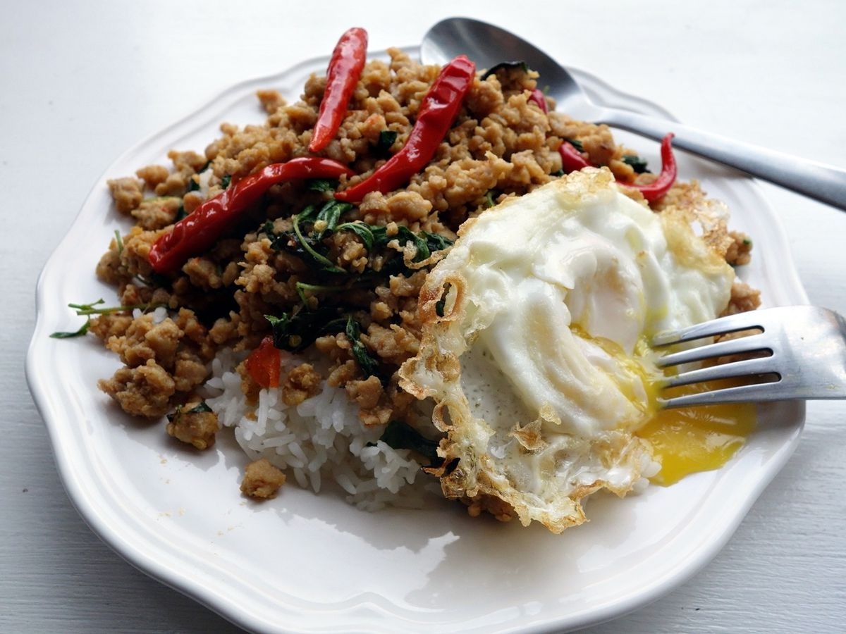 A view of a dish with ground pork, served with a fried egg on top of white rice.