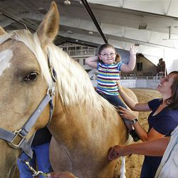 Katelyn Newton is all smiles as she rides Summer, while Valerie Duffin, center, and Cindy Becker help, at the Buffalo Ranch in Farmington on Thursday. Becker started the nonprofit group Therapeutic Assets to provide physical, emotional, and behavioral therapy for children and adults through riding.