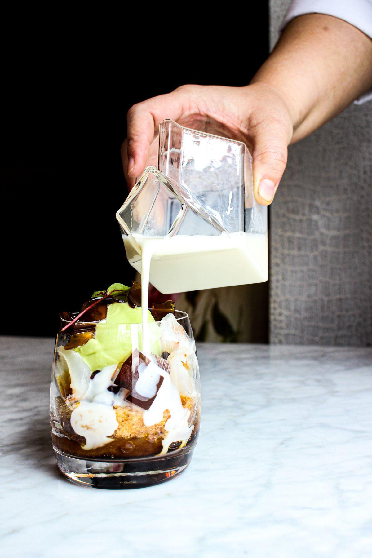 A person pours cream into an upscale riff on a bubble tea.