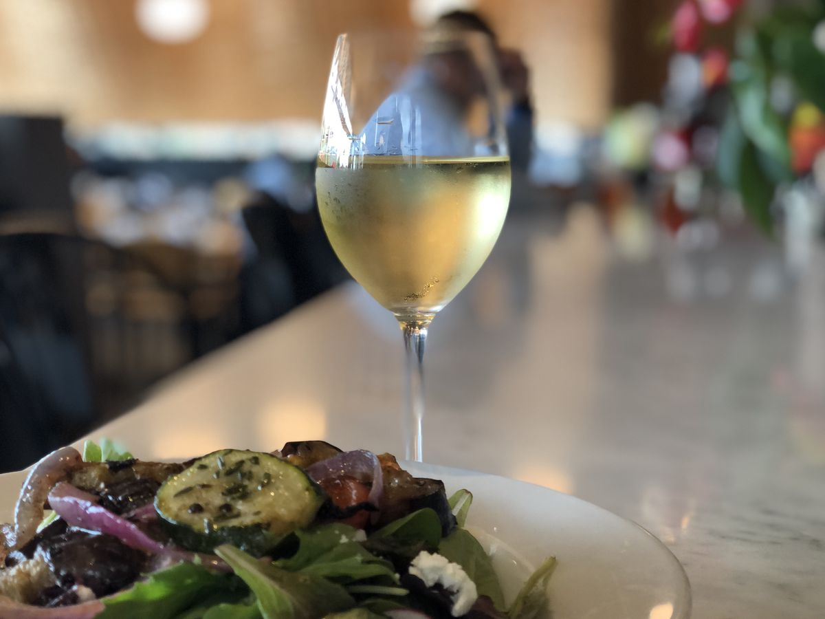 A glass of white wine next to a salad.