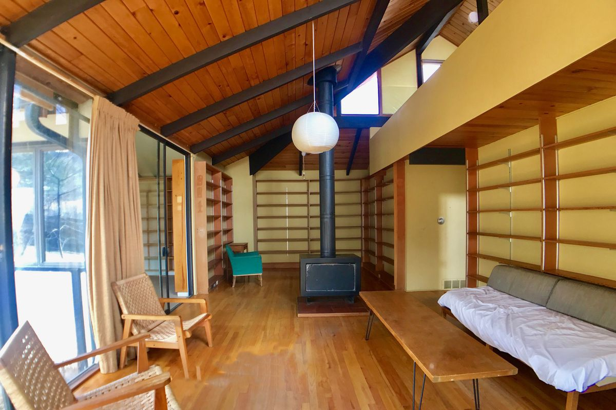 Interior shot of living room with high vaulted and beamed ceilings, wall of windows, and plenty of built-in shelving.
