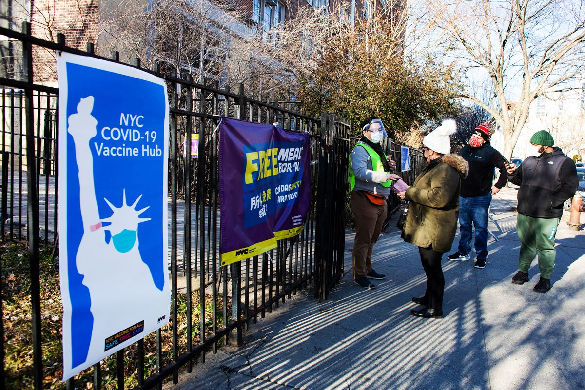 """A sign on a fence lining a sidewalk features a silhouette of the Statue of Liberty wearing a breathing mask and the words """"NYC Covid-19 Vaccine Hub."""" People stand nearby."""