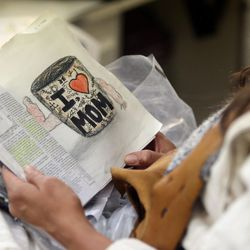 Kymberly Mellen, who plays Sariah, reads the Book of Mormon while getting her hair done on the set of the Book of Mormon Visual Library at LDS Motion Picture Studios South Campus near Goshen on Friday, July 7, 2017. Her daughter made her the drawing that she is using as a bookmark.