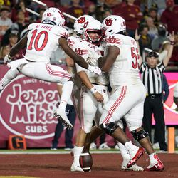 Utah quarterback Cameron Rising, center, celebrates his rushing touchdown with teammates during the second half of an NCAA college football game against Southern California on Saturday, Oct. 9, 2021, in Los Angeles.