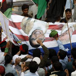 """Pakistani protesters hold a banner depicting U.S. President Barack Obama and pastor Terry Jones during a rally in Peshawar, Pakistan as a part of widespread anger across the Muslim world about a film ridiculing Islam's Prophet Muhammad, on Thursday, Sept. 20, 2012. Recent images of angry mobs in Arab cities burning American flags and attacking U.S. diplomatic posts suggest the Muslim world is no less enraged at the United States than when President George W. Bush had to duck shoes hurled at him in Baghdad. But more than three years after Obama declared in Cairo that he would seek """"a new beginning"""" in U.S.-Muslim relations, a closer look reveals strides as well as setbacks."""