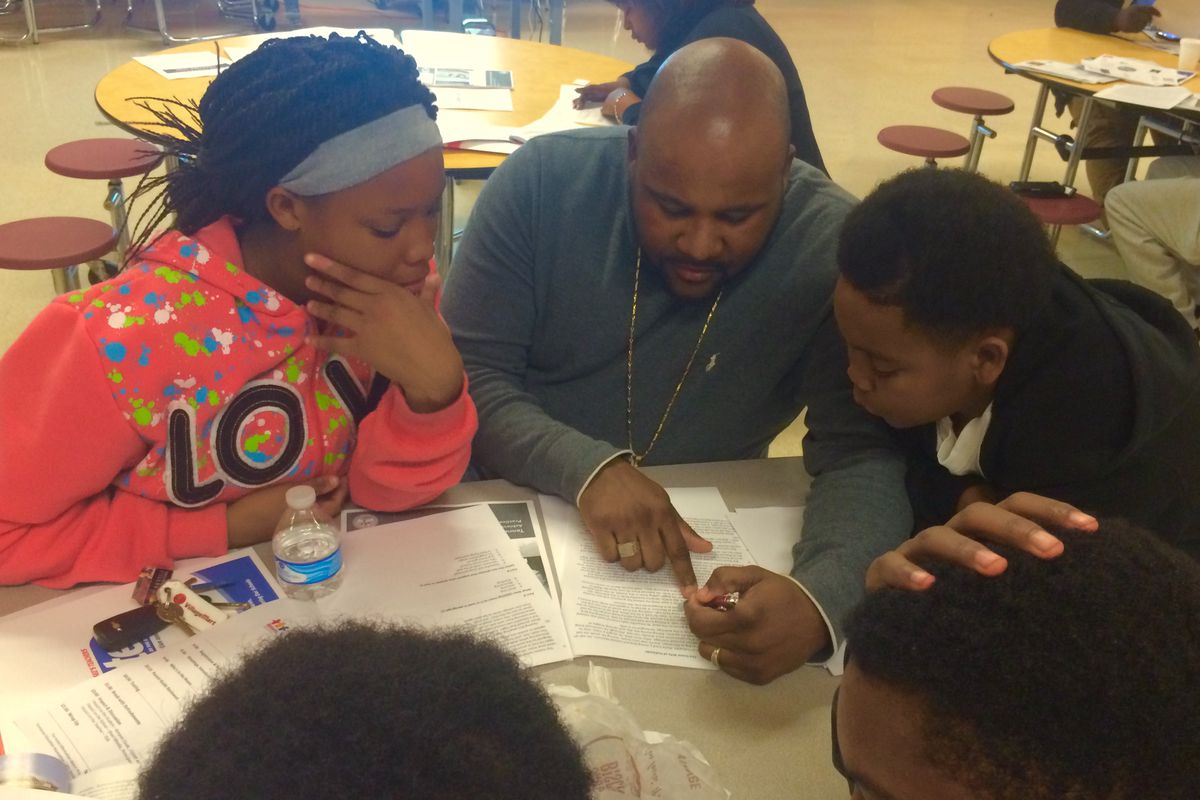 Shamaine Walls reviews TNReady practice questions with his niece Angelica Walls and nephew Mario Taylor at a TNReady information event sponsored in Memphis by the Tennessee Education Association.