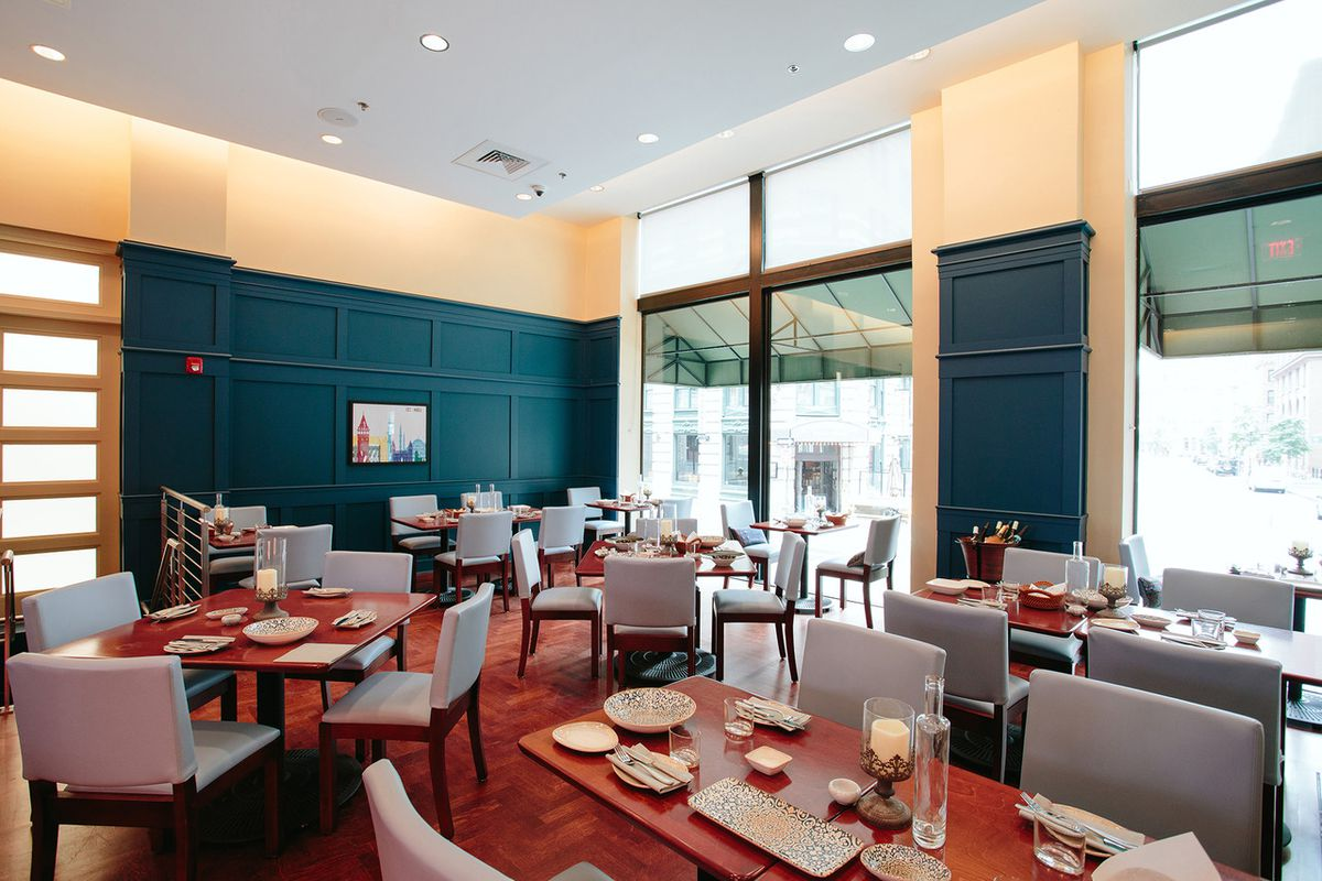 Sunlit interior of a small upscale restaurant, featuring turquoise wall paneling, a wooden floor, and elegant gray and wooden chairs