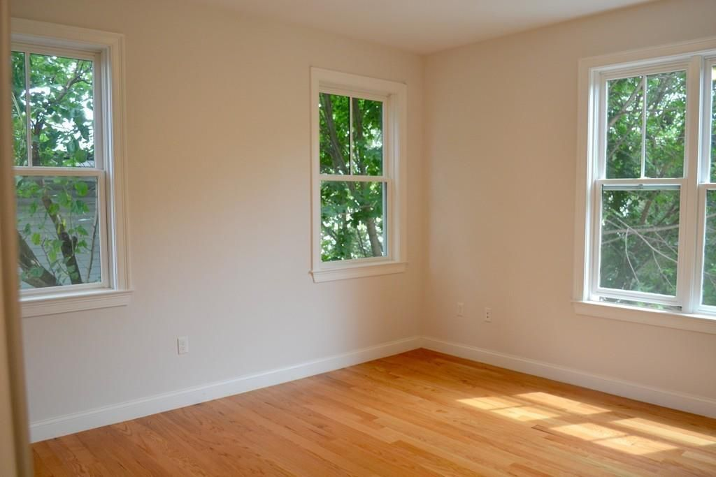 Another empty room with sets of windows facing each other at a corner.